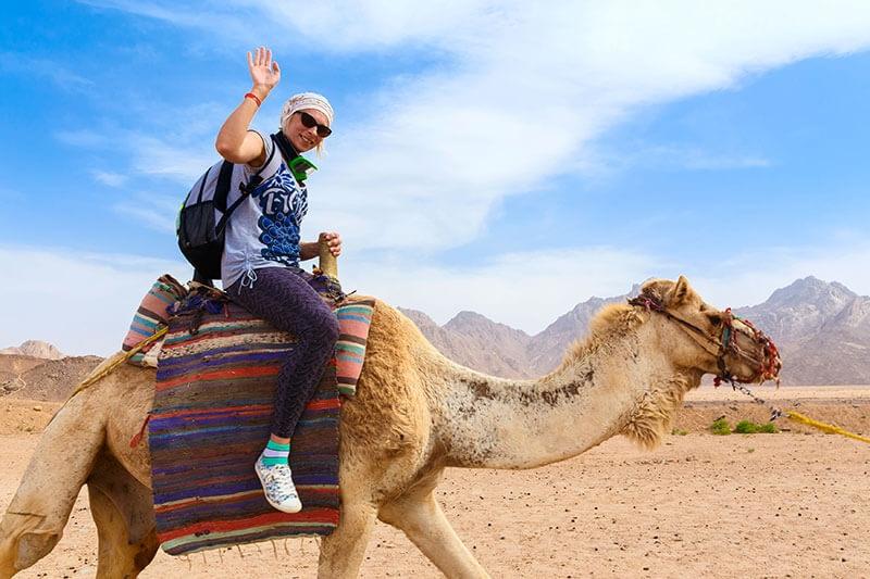 Solo Women Traveler rides a camel in the desert